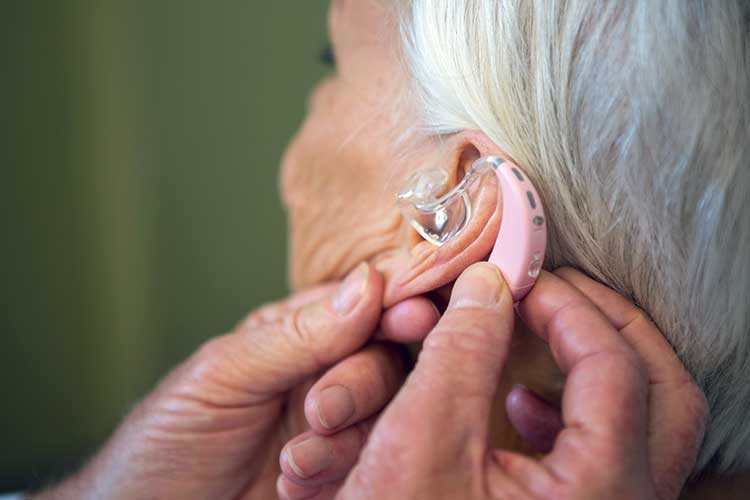 worker inserting hearing aid